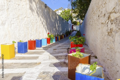 Mykonos alley, Greece. A typical greek island cobbled alley in Chora, Mykonos, Greece decorated with colourful flower pots of geranium and surrounded by whitewashed architecture.