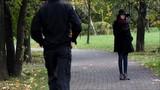 Девушка в осеннем парке с мобильным телефоном. Мимо проходит парень и оборачивается на красивую девушку. Она в шляпе и пальто. Осень, холодно