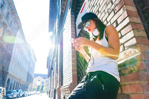 Hip hop girl with headphones in a urban environment Poster