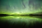 Northern lights on the night sky.Green light reflection on the water of a lake.