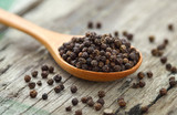 Whole black pepper on wooden spoon
