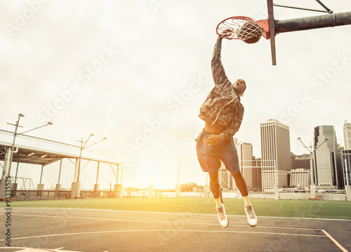 Fotografiet Street basketball player performing power slum dunk