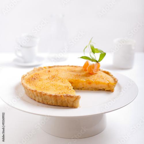 """Tangerine creme brulee tart on a white background ..."