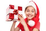 Fototapety Świąteczne marzenia, Magiczny czas świąt. Szczęśliwe dziecko w czapce św. Mikołaja z zapakowanym prezentem