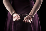 submissive woman wearing a purple dress in metal handcuffs on bl