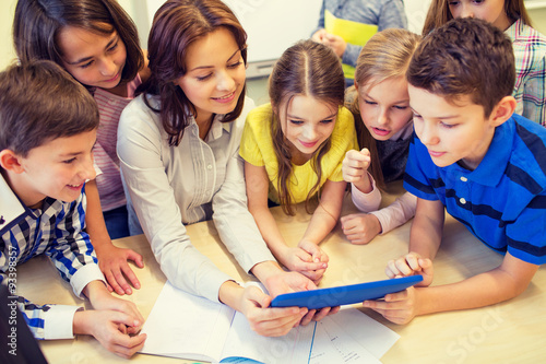 Poster group of kids with teacher and tablet pc at school