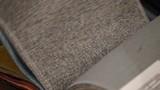 textiles. Girl leafing through tissue samples for sofa upholstery