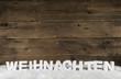 Weihnachtlicher Holz Hintergrund in braun mit Text Weihnachten in weiß