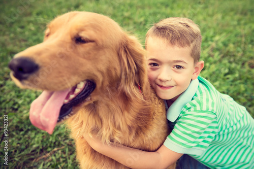 Fototapeta Cute little boy hugging his golden retriever pet dog