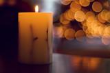 Vela con luces del árbol de Navidad desenfocadas de fondo.