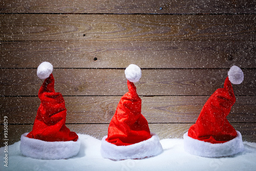 Fototapeta Santa hats in snow with wooden background