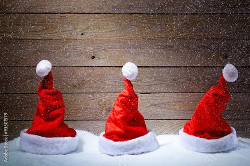 Naklejka Santa hats in snow with wooden background