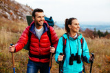 Fototapety Backpackers couple hiking during fall with sticks