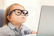 Smart toddler girl wearing big glasses while using her laptop