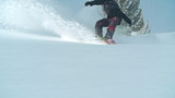Slow motion shot of skilled snowboarder enjoying freeride on fresh fallen snow