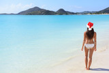 Woman in Santa hat on beach travel vacation