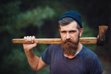 Fototapety brutal brunette bearded man in warm hat with a hatchet in the woods on a background of trees