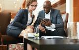 Fototapety Businesspeople looking at digital tablet
