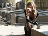 Sad woman holding bunch of flowers near a grave