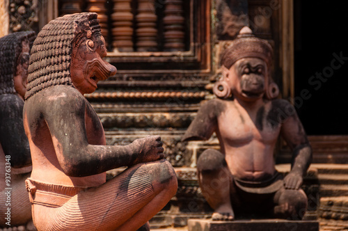 Stone sculputure sitting in front of temple B Poster