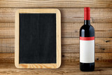 Bottle of red wine and blank blackboard on wooden background