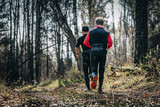 two men runner running in autumn forest during mountain marathon. view from back