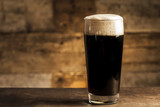 Fototapety Black beer on wooden background