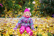 Happy little child, baby girl laughing and playing in the autumn