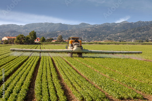 Poster agriculture, tractor spraying pesticides on field farm