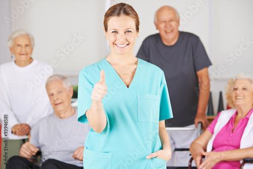 Leinwanddruck Bild Krankenpfleger hält Daumen hoch vor Gruppe Senioren