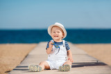 Fototapety Portrait of a happy child with a hat on the beach