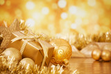 Fototapety Christmas scene with gold baubles and gift, gold background