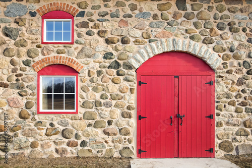 fototapeta na ścianę Bright Red Arched Door and Windows in a Stone Wall