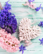 Hyacinths flowers and decorative heart on wooden table