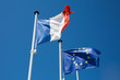 Flags of the European Union and France in clear windy day
