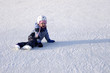 A Young Skater sitting on ice