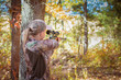 Woman aiming a rifle in a fall setting
