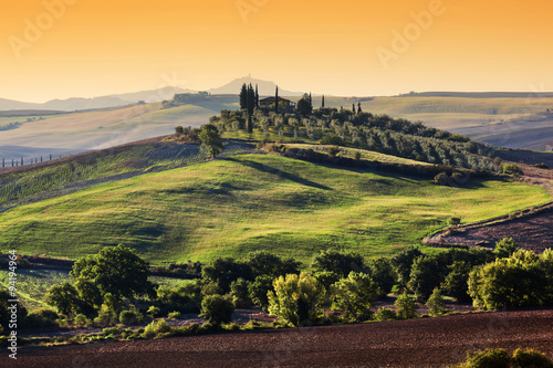 Tuscany landscape at sunrise. Tuscan farm house, green hills. Plakat