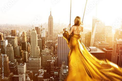 Femme sur une balançoire au-dessus de New York City Poster