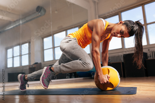 Poster Woman doing intense core workout in gym