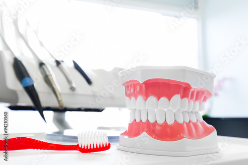 Poster Clean teeth denture, dental jaw model and toothbrush in dentist's office
