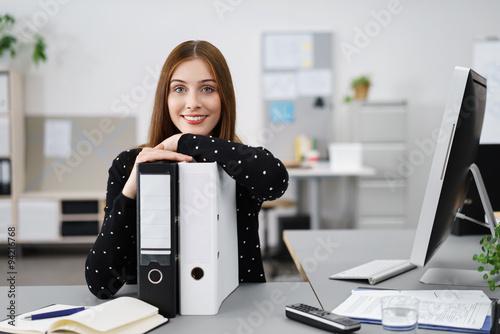 lächelnde frau im büro stützt sich auf aktenordner © contrastwerkstatt
