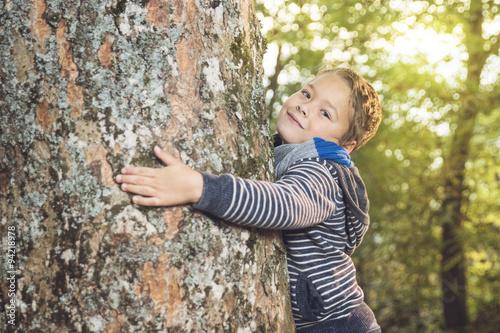 Poster Bengel hält einen uralten Baum fest