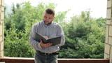 Man reading notes in calendar on terrace