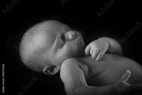Poszter Sleeping Newborn Baby with black background