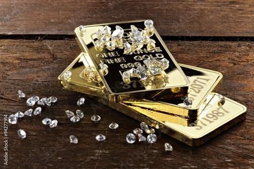 fototapeta na ścianę Goldbarren und geschliffene Diamanten auf rustikalem Holzhintergrund