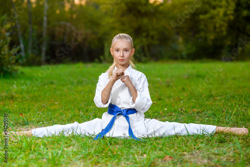 Fototapeta girl in white kimono during training karate exercises at summer