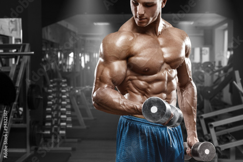 fototapeta na ścianę Muscular man working out in gym doing exercises with dumbbells at biceps, strong male naked torso abs
