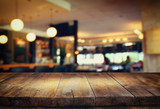 Fototapety image of wooden table in front of abstract blurred background of restaurant lights