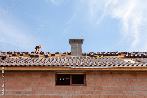 Staande foto Industrial geb. Roofer preparing tile to install on the new roof. Roof Tile Installation